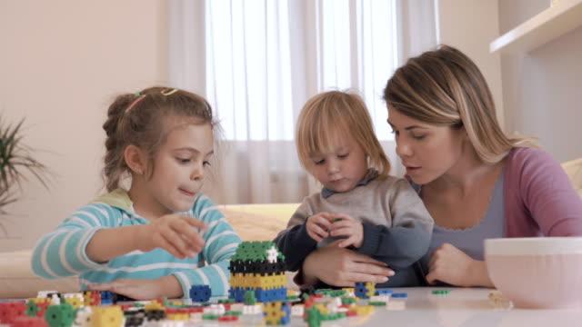 Kleine kinderen en hun moeder spelen met puzzels thuis.