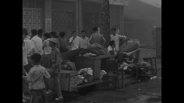 small children hiding underneath a truck with a pan to a large fire with wind blowing through trees / displaced people on city street with heavy... - south vietnam stock videos & royalty-free footage