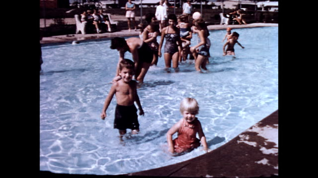 / small children in clear blue pool on sunny day / moms play with children / toddler wades across the pool smiling children playing in levittown pa... - levittown pennsylvania stock videos and b-roll footage