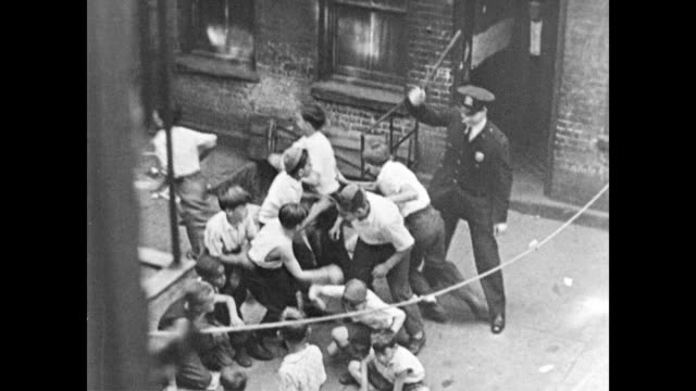 vídeos de stock e filmes b-roll de / cu small children's faces / children playing in the street / children inside tenement houses / policeman chases children in the street poor... - 1960