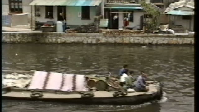 MS Small Chinese motorized cargo boat going down a river / Shanghai China