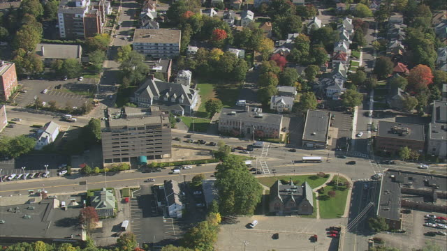 AERIAL Small city with commercial buildings, trees, and traffic on city streets / Quincy, Massachusetts, United States