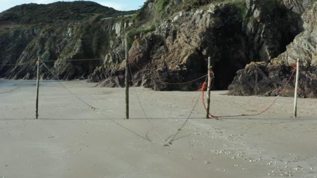 vídeos y material grabado en eventos de stock de pequeños acantilados en una playa rocosa desierta en marea baja en el suroeste de escocia - brightly lit
