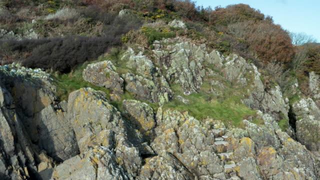 スコットランド南西部の干潮時の無人岩のビーチの小さな崖 - brightly lit点の映像素材/bロール
