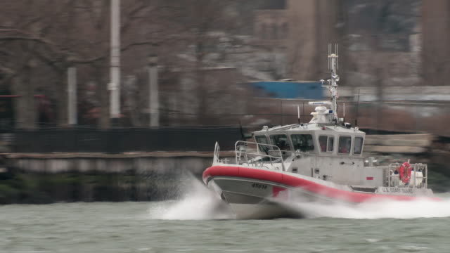 a small coast guard patrol boat travels up a busy waterway in nj.  it's police lights are flashing - police boat stock videos and b-roll footage