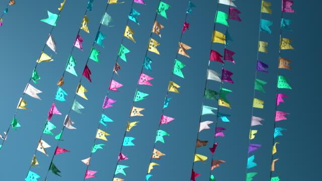 vídeos de stock, filmes e b-roll de small colored paper banners against the blue sky - tradição