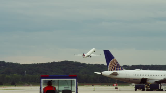 A small commercial passenger jet takes off from an airport runway. The tail of a parked aircraft and a luggage tug in the foreground.