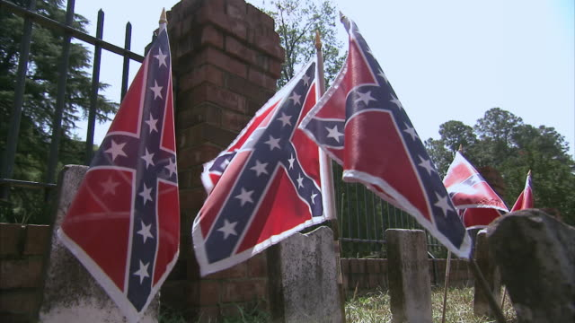 cu small confederate flags and old tombstones in front of wrought iron fence / columbia, south carolina, united states - confederate flag stock videos and b-roll footage