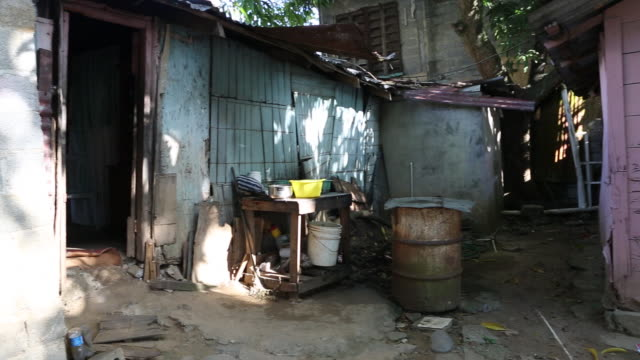 santa domingo dominican republic november 29 2012 a small cottage with a thin roof can be seen at the slum 'los alcarrizos' in santa domingo a woman... - santo domingo dominican republic stock videos & royalty-free footage