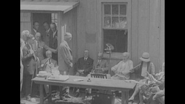 WS small crowd mills about around wooden building / VS outside the building Thomas Edison sits next to Henry Ford and listens as man speaks woman...