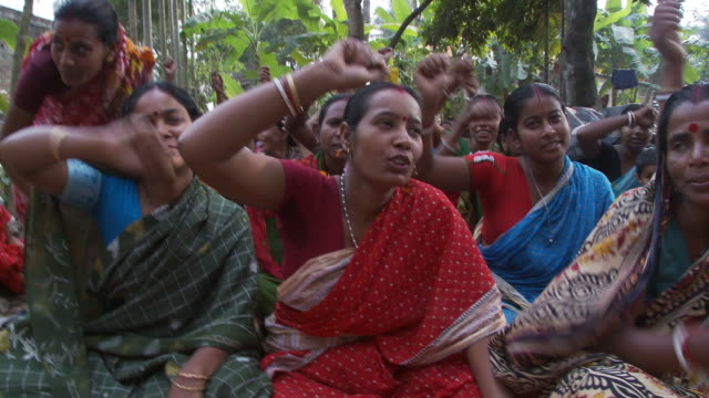 small crowd of indian women sitting on the ground, chanting and waving arms. - sitting on ground stock videos & royalty-free footage