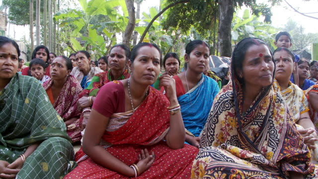 a small crowd of indian women sitting on the ground, listening to an unseen speaker. - sitting on ground stock videos & royalty-free footage