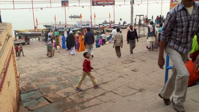 small crowd of people at the wharf of an indian city. - palapa stock videos & royalty-free footage