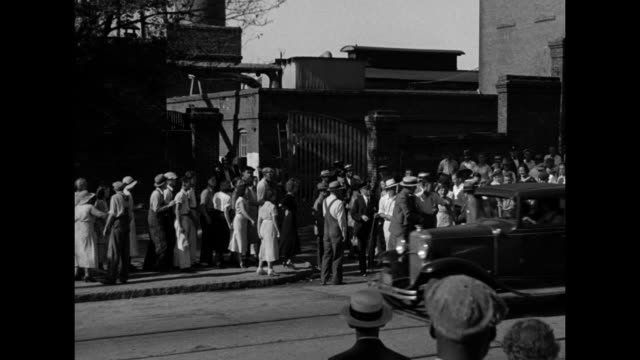 ms small crowd of women on far sidewalk as car pulls out of mill gates men stand on near sidewalk / ms crowd of men women and children on tree lined... - 1934 stock videos & royalty-free footage