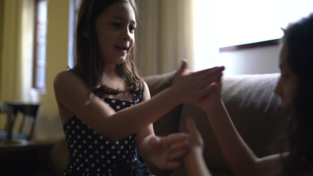 vídeos de stock e filmes b-roll de small cute girl friends playing with hands at home - jogo de lazer