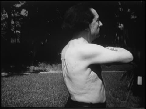 b/w 1951 side view small darts flying into back of shirtless man / newsreel - 1951点の映像素材/bロール