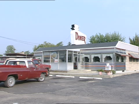 small diner in rural area diner rooftop sign w/ chef's hat pickup trucks parked in parking spots in front of diner male exiting truck breakfast food... - chef's hat stock videos and b-roll footage