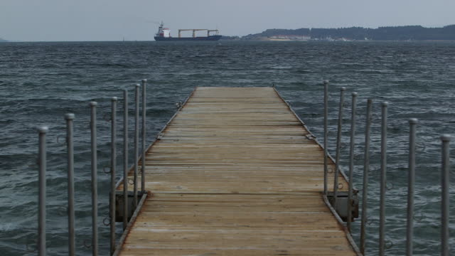 small dock w barge in distance - molo video stock e b–roll