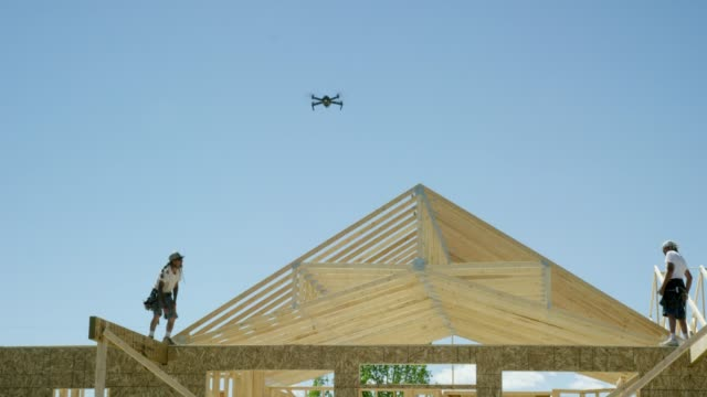 A Small Drone Quadcopter Flies over a Construction Site as Male Construction Workers Frame a House on a Clear, Sunny Day