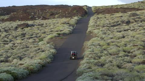 vídeos y material grabado en eventos de stock de a small electric car travels along a coastal road on the island of el hierro. - coche eléctrico coche alternativo