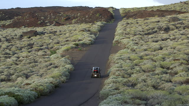 a small electric car travels along a coastal road on the island of el hierro. - small stock videos and b-roll footage