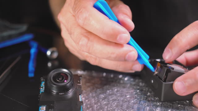 small electronic repair. close-up video of hands of man assembling disassembled action camera. - dismantling stock videos & royalty-free footage