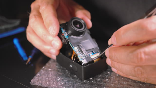 small electronic repair. close-up video of hands of man servicing an action camera. - electronics industry stock videos & royalty-free footage