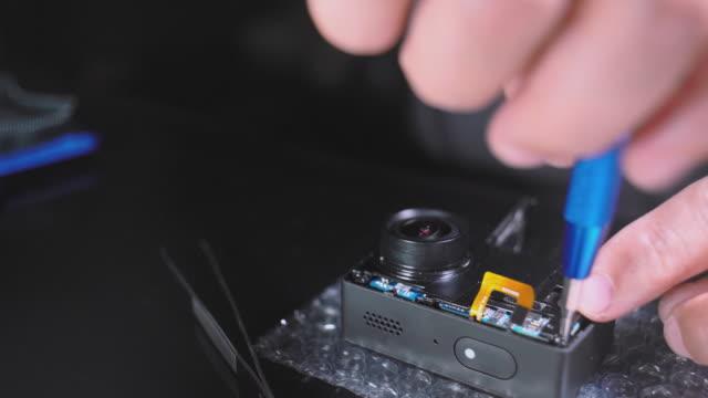 vidéos et rushes de petite réparation électronique. vidéo en gros plan des mains de l'homme servant une caméra d'action. - un seul objet