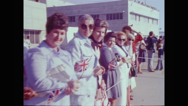 stockvideo's en b-roll-footage met a small excited crowd wave union jack flags at edwards air force base - 1977