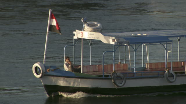 a small ferry boat sails along the nile near aswan. - ausflugsboot stock-videos und b-roll-filmmaterial