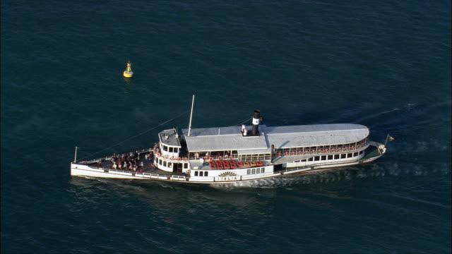 Small Ferry Leaving Sirmione  - Aerial View - Lombardy, Provincia di Brescia, Sirmione, Italy