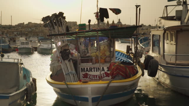stockvideo's en b-roll-footage met small fishing boat at sunset - malta - klein
