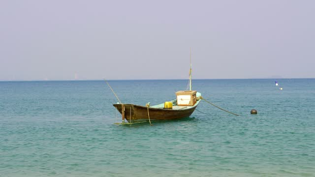 a small fishing boat docked on the beach on koh samet, rayong, thailand. - rowing boat stock videos & royalty-free footage