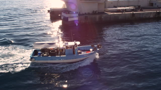 small fishing boat entering monaco port hercules harbour and motoring past expensive yachts - monaco stock-videos und b-roll-filmmaterial