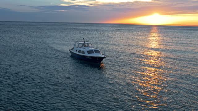 Luchtfoto kleine vissersboot rijden op zee bij zonsondergang