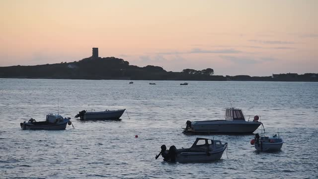 vídeos de stock e filmes b-roll de small fishing boats anchored on the calm ocean in st. peter port, guernsey, channel islands, uk during the golden hour.- wide shot - ancorado
