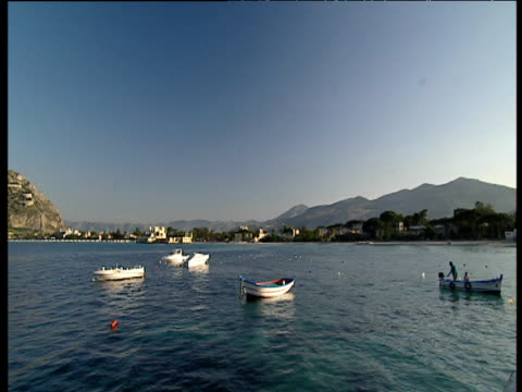 small fishing boats in harbour pan left mountains in background mondelo sicily - recreational pursuit stock videos & royalty-free footage