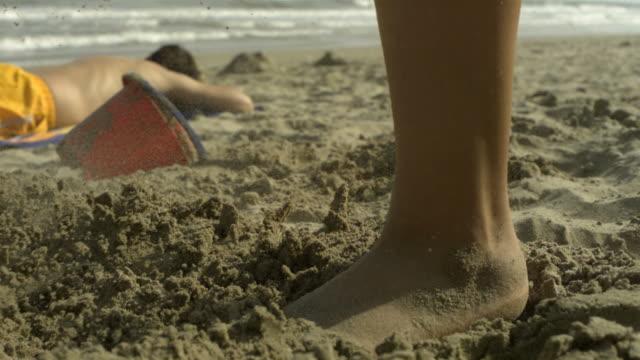 vídeos de stock, filmes e b-roll de slo mo small foot kicking in sandcastle, spain - muito pequeno