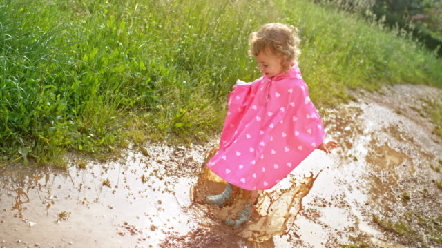 slo mo small girl in a pink raincoat jumping in a muddy puddle - raincoat stock videos & royalty-free footage