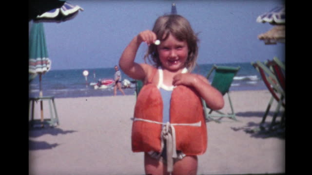 1964 small girl in life vest shows shell she found - scoperta video stock e b–roll