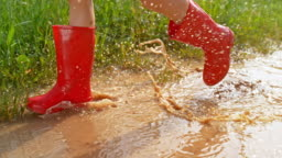 SLO MO Small girl in red rain boots running across a muddy puddle in sunshine