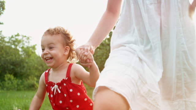 slo mo ts small girl laughing while running across a meadow holding hands with big sister - white dress stock videos & royalty-free footage