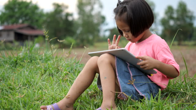 small girl on rural scene with a tablet pc. - white dress stock videos & royalty-free footage