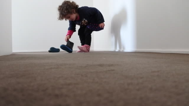 Small girl putting on boots