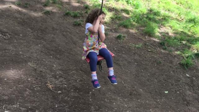 Small Girl Swinging on a Tree Swing