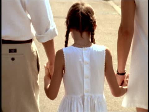 stockvideo's en b-roll-footage met rear view small girl walking hand in hand with couple outdoors / girl turns + smiles at camera - zij aan zij