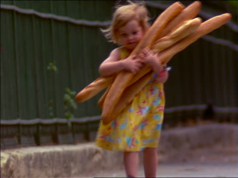 vídeos de stock, filmes e b-roll de small girl with armload of baguettes smiling + running towards camera / paris, france - french culture