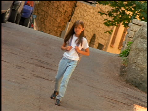 stockvideo's en b-roll-footage met canted small girl with backpack walks on street toward camera / corsica - alleen meisjes