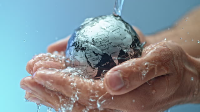 vídeos de stock e filmes b-roll de slo mo small globe in the woman's hands being watered with crystal clear water from above - liquid crystal display
