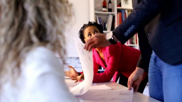 liten grupp arkitekter. hektisk dag på jobbet. icke-kaukasiska kvinnliga ledare - tre människor bildbanksvideor och videomaterial från bakom kulisserna